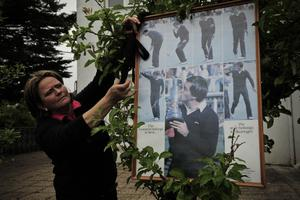 A relative of Spanish professional golfer Seve Ballesteros fixes a black ribbon beside a poster with several photos of Ballesteros during his funeral service in the small town of Pedrena, Spain