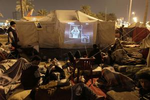 Bahraini anti-government demonstrators watch a soccer game between Barcelona and Arsenal on a TV projector while camping out in protest at the Pearl roundabout in Manama.
