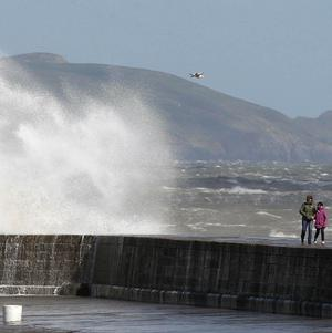 People walk on Howth Pier in north Dublin, as winds batter the coastline