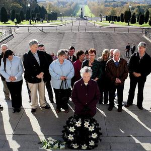 Kathleen Armstrong (centre with wreath), whose husband Charlie was murdered by the IRA in 1981, lays a wreath at the steps of Stormont