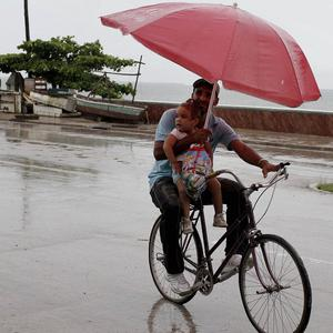 A man balances a child and umbrella on his bike as it rains during the approach of Hurricane Sandy in Manzanillo, Cuba (AP)