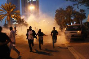MANAMA, BAHRAIN - FEBRUARY 18:  Protesters run from a cloud of teargas during a clash with Bahraini security forces near the Pearl roundabout on February 18, 2011 in Manama, Bahrain. Protesters said that the army fired on them with live rounds, followed by teargas which drove the demonstrators back. There are unconfirmed reports that there are four dead in the clashes.  (Photo by John Moore/Getty Images)  ***BESTPIX***