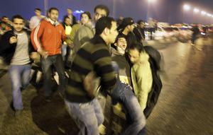 A wounded protester is carried away by others during clashes in Cairo, Egypt, in the early hours of Wednesday, Jan. 26, 2011. Egyptian police fired tear gas and rubber bullets and beat protesters to clear thousands of people from a central Cairo square Wednesday after the biggest demonstrations in years against President Hosni Mubarak's authoritarian rule. (AP Photo/Ben Curtis)