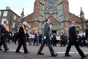 Orange Order members march passed St Patrick's Church in Belfast, during a massive loyal order parade to mark the centenary of the signing of the pro-Union Ulster Covenant