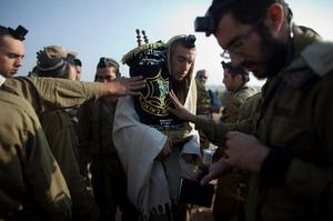 ISRAEL/GAZA BORDER, ISRAEL- NOVEMBER 19:  (ISRAEL OUT) Israeli soldiers perform their morning prayers in a deployment area on November 19, 2012 on Israel's border with the Gaza Strip. The death toll has risen to at least 85 killed in the air strikes, according to hospital officials, on day six since the launch of operation 'Pillar of Defence.'  (Photo by Uriel Sinai/Getty Images)