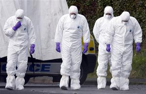 Police forensic officers examine the scene at the Massereene army barracks in Antrim, west of Belfast, Northern Ireland, Sunday, March, 8, 2009 after two British soldiers were shot to death and four other people wounded in a drive-by ambush that politicians blamed on IRA dissidents. Suspected IRA dissidents who opened fire on British soldiers and pizza delivery men outside an army base shot their victims again as they lay wounded on the ground, police said Sunday. Two soldiers died and four other people, including two men delivering pizzas, remained hospitalized with serious wounds following Saturday night's attack at the entrance to Massereene army barracks in Antrim, west of Belfast.   (AP Photo/Peter Morrison)