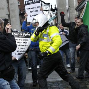 Gardai hold back Sinn Fein protesters at government buildings (AP)