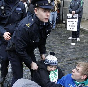 Gardai remove Sinn Fein protesters from inside the gates of government buildings (AP)