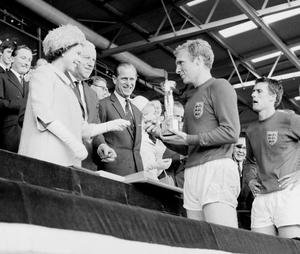 File photo dated 30/07/1966 of England captain Bobby Moore holding the Jules Rimet Trophy, collected from the Queen, after leading his team to a 4-2 victory over West Germany, in an exciting World Cup Final that went to extra time at Wembley, London. PRESS ASSOCIATION Photo.