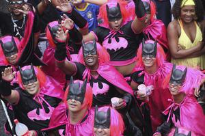 """Men, disguised as """"Batman,"""" dance during a """"Bola Preta"""" block parade in Rio de Janeiro, Brazil, Saturday, March 5, 2011. The five-day annual carnival celebration officially started Friday and is expected to draw about 756,000 visitors, both foreign and Brazilian, who will pack hotels to nearly 100 percent capacity and spend about $559 million, according to Rio state's tourism department. (AP Photo/Silvia Izquierdo)"""