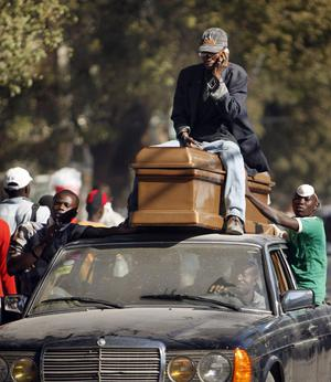 People ride with a coffin on top of a car as they arrive at the morgue in the aftermath of Tuesday's earthquake in Port-au-Prince, Friday, Jan. 15, 2010.