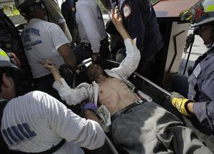 A United Nations worker, who was just rescued from the collapsed United Nations headquarters building, responds to questions from medical personnel as he is carried to a temporary clinic in Port-au- Prince, Sunday, Jan. 17, 2010.