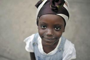 A girl smiles at Park Boyer, which has been turned into a temporary camp for people whose homes have been destroyed, in the Petionville neighborhood of Port-au-Prince on Saturday, Jan. 16, 2010. (AP Photo/Michael Laughlin, Sun-Sentinel)