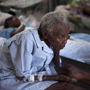 A woman suffering from cholera symptoms is treated at the St Nicholas hospital in Saint Marc, Haiti (AP)