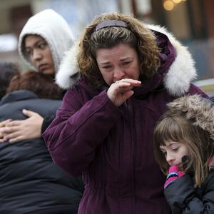 Mourners grieve at one of the makeshift memorials for victims of the Sandy Hook Elementary School shooting in Newtown, Connecticut (AP)
