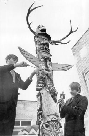 Robert McConnell, of Whitehouse (left), and William McLaughlin, Shore Road, spent two months and many hours of research to make this totem pole as authentic as possible. Now that the piece has been finished it will stand at their school, Dunlambert Secondary, in place of honour in a courtyard, 1968.