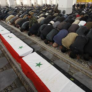 Syrian mourners pray in front of the coffins of 11 Syrian police officers who were killed in an explosion in the Midan neighborhood of Damascus (AP)