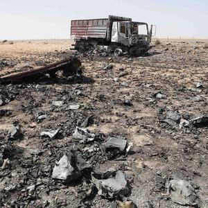 Charred metal and debris lies on the ground near the burned remains of a truck in the Libyan city of Ajdabiya (AP)