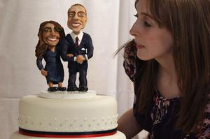 LONDON, ENGLAND - APRIL 21:  A woman admires a cake featuring figurines of Prince William and Kate Middleton at an exhibition of Royal Wedding cakes on April 21, 2011 in London, England. The cake features in the 'Let Them Eat Cake' exhibition inside Wellington Arch on Hyde Park Corner and is open to the public over Easter from April 22-25, 2011.  (Photo by Oli Scarff/Getty Images)