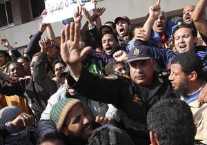 In this photo taken Saturday, Jan. 29, 2011, a police officer gestures as he joins anti-government protestors in Suez, Egypt. The Arab world's most populous nation appeared to be swiftly moving closer to a point at which it either dissolves into widespread chaos or the military expands its presence and control of the streets. (AP Photo)