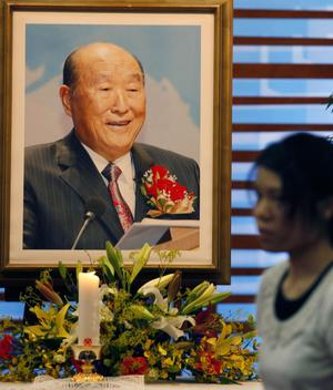 A woman walks past the picture of the Rev. Sun Myung Moon at a Unification Church in Tokyo, Monday, Sept. 3, 2012. The Unification Church's founder Moon, the self-proclaimed messiah who founded the church, died Monday, Sept. 3, 2012, at a church-owned hospital near his home in Gapyeong County, northeast of Seoul, church officials said. He was 92.(AP Photo/Koji Sasahara)