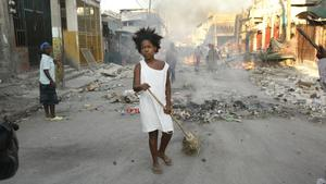 A woman sweeps debris out of the street in Port-au-Prince, Haiti, Monday, Jan. 18, 2010. On the streets, people are still dying, pregnant women are giving birth and the injured are showing up in wheelbarrows and on people's backs at hurriedly erected field hospitals. (AP Photo/Gerald Herbert)