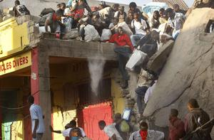 People take goods from buildings collapsed during last week's earthquake in the market area of Port-au-Prince, Haiti, Monday, Jan. 18, 2010. (AP Photo/Gerald Herbert)