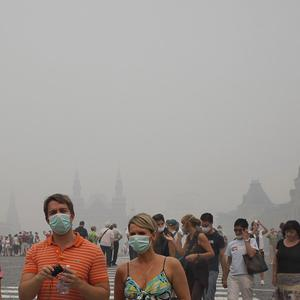 Tourists wearing face masks walk across Red Square in a thick blanket of smog (AP)