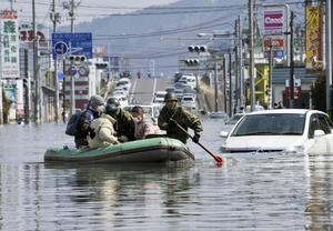 Members of Japan Self-Defense Forces rescue people stranded at a flooded city center in Ishinomaki, Miyagi Prefecture, northern Japan, Sunday, March 13, 2011, two days after a powerful earthquake-triggered tsunami hit the country's east coast. (AP Photo/Kyodo News) JAPAN OUT, MANDATORY CREDIT, NO SALES IN CHINA, HONG  KONG, JAPAN, SOUTH KOREA AND FRANCE