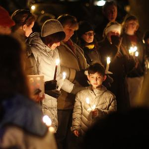 Mourners gather for a candlelight vigil to remember the shooting victims (AP)