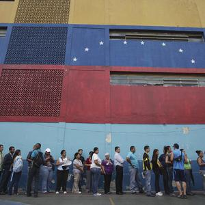 People wait in line to cast their ballots in the opposition primary election in the Petare neighborhood of Caracas, Venezuela (AP)