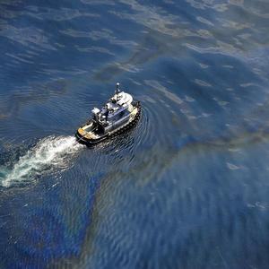 A boat moves through oily water at the site of the Deepwater Horizon oil spill in the Gulf of Mexico