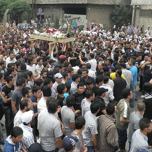 Anti-Syrian regime mourners carry the body of an activist during his funeral procession in Damascus (AP)