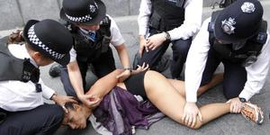 """British police officers arrest a supporter of Ukrainian FEMEN movement protesting in a """"Islamic Marathon"""" against what they claim are bloody Islamist regimes that are supported by the International Olympic Committee outside City Hall in London, Thursday, Aug. 2, 2012. (AP Photo/Sang Tan)"""