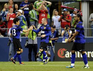 Manchester United's Wayne Rooney, center, is greeted by Manchester United's Ji-Sung Park left, after Rooney scored a goal in the second half of a friendly soccer match, Wednesday, July 20, 2011, in Seattle. Manchester United beat the Sounders, 7-0. (AP Photo/The News Tribune, Jeremy Harrison)