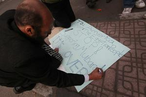 CAIRO, EGYPT - JANUARY 30:  A protestor writes a message on a placard in Tahrir Square on January 30, 2011 in Cairo, Egypt. Cairo remained in a state of flux and marchers continued to protest in the streets and defy curfew, demanding the resignation of Egyptian president Hosni Mubarek. As President Mubarak struggles to regain control after five days of protests he has appointed Omar Suleiman as vice-president. The present death toll stands at 100 and up to 2,000 people are thought to have been injured during the clashes which started last Tuesday. Overnight it was reported that thousands of inmates from the Wadi Naturn prison had escaped and that Egyptians were forming vigilante groups in order to protect their homes.   (Photo by Peter Macdiarmid/Getty Images)