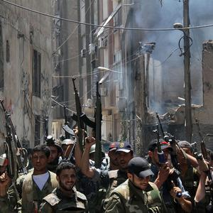 Syrian soldiers celebrate after they regained control of the district of Midan, in the southern part of Damascus (AP/Bassem Tellawi)