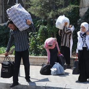 Syrians carry their belongings as they cross into Lebanon at the border crossing point in Masnaa, eastern Lebanon (AP)