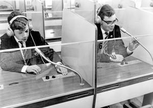 "Stephen (left) and Peter Weil in the language lab at Methodist College. The students listen to the teacher's voice, then record their own voices. When the tape is played back they can make comparisons. The system is monitored by the teacher, who can ""break in"" to give individual instruction to any pupil."