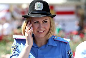 A Ukranian Policewoman watches England fans outside the Golden Lion in Donetsk, Ukraine