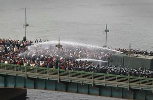 CAIRO, EGYPT - JANUARY 28:  Riot police fire water cannons at protestors attempting to cross the Kasr Al Nile Bridge on January 28, 2011 in downtown  Cairo, Egypt. Thousands of police are on the streets of the capital and hundreds of arrests have been made in an attempt to quell anti-government demonstrations.  (Photo by Peter Macdiarmid/Getty Images)  ***BESTPIX***