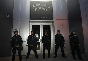 OAKLAND, CA - NOVEMBER 12:  Oakland police officers block the entrance to police headquarters as Occupy Oakland protesters march through the streets on November 12, 2011 in Oakland, California.  In the wake of violent confrontations with police, vandalism and the recent shooting near the encampment, Oakland mayor Jean Quan and city administrators have issued eviction notices to protesters at the Occupy Oakland encampment and have asked them to leave immediately.  (Photo by Justin Sullivan/Getty Images)