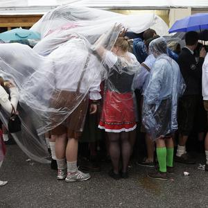 People wait for the opening of the famous Oktoberfest in front of a beer tent during heavy rain in Munich, southern Germany (AP)