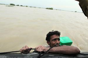 Pakistani flood victim Mohammed Nawaz hangs onto a moving raft as he is rescued by the Pakistan Navy