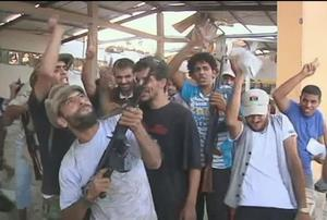 In this image provided by Associated Press Television News, Libyan rebels celebrate in west of Tripoli, Libya Sunday, Aug. 21, 2011. The rebels raced into Tripoli Sunday and met little resistance as Moammar Gadhafi's defenders melted away and his 42-year rule rapidly crumbled. The euphoric fighters celebrated with residents of the capital in Green Square, the symbolic heart of the fading regime. (AP Photo/Associated Press Television News)