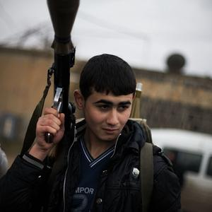 A Free Syrian Army fighter holds his weapon as he prepares himself for advance, close to a military base, near Azaz (AP)