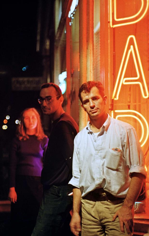 """Author Jack Kerouac outside the bar Kettle of Fish on New York's MacDougal Street, Oct. 15, 1958 after leaving a publisher's party for his book """"The Dharma Bums."""" The woman in the background is author Joyce Johnson."""