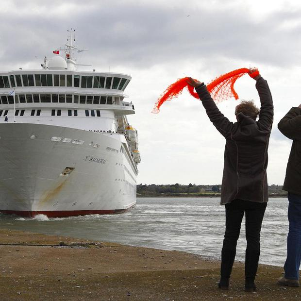 People wave at the Balmoral cruise ship wave as it leaves Southampton docks on the official Titanic centenary voyage