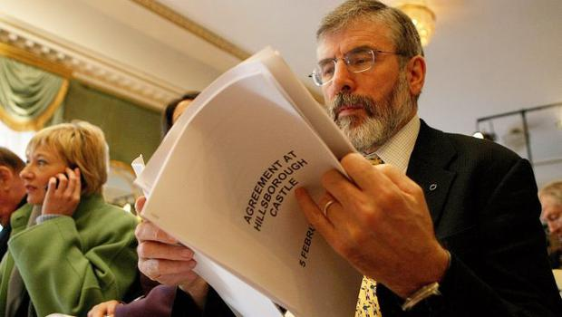 Sinn Fein's Gerry Adams looks at a copy of the agreement after a deal was announced about Northern Ireland's power-sharing government at the press conference in Hillsborough