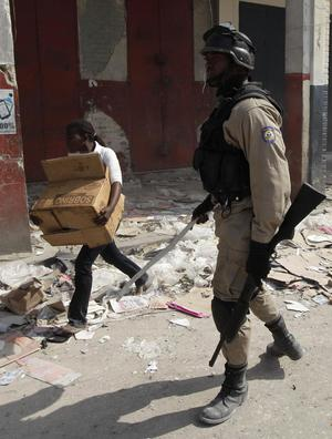 A woman run with stolen items from a collapsed store as a Haitian police officer looks on in Port-au-Prince, Sunday, Jan. 17, 2010.